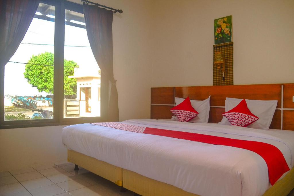 A bed or beds in a room at OYO 798 Yokima Beach Hotel