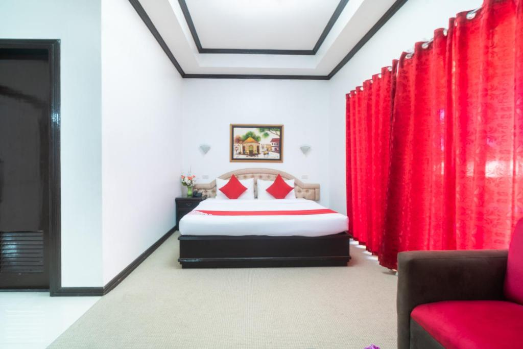 A bed or beds in a room at OYO 197 Sunny Point Hotel