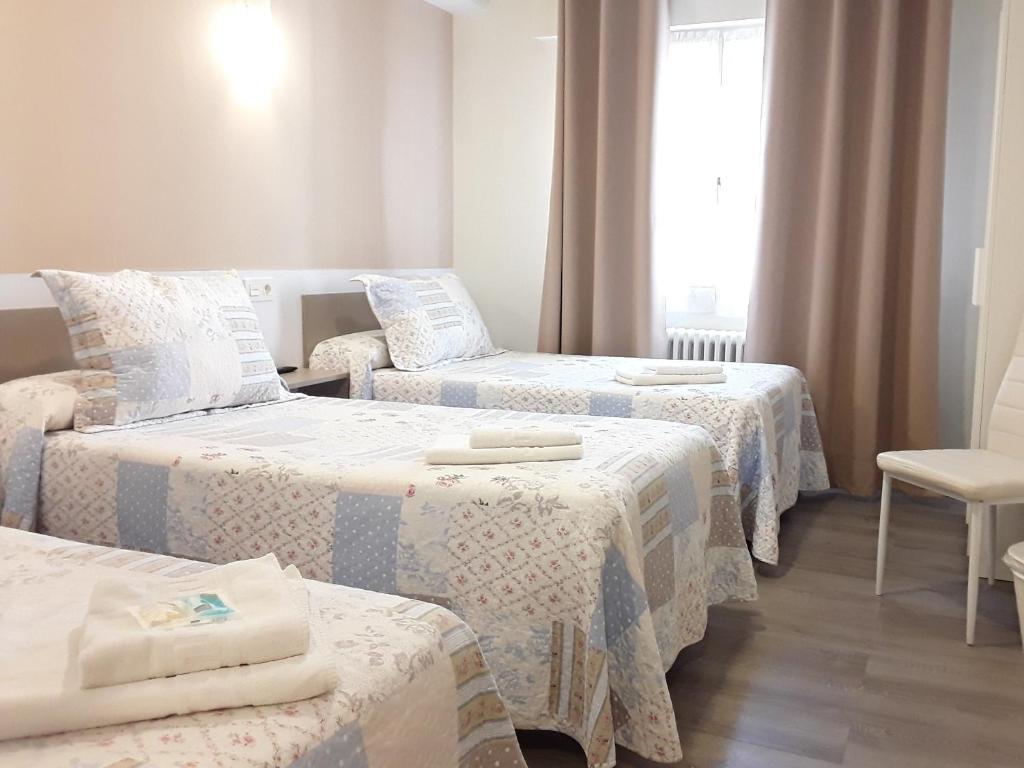 A bed or beds in a room at Pension Principado