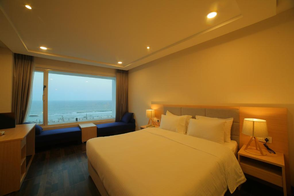 A bed or beds in a room at Bay View Hotel Vizag