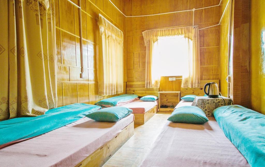 A bed or beds in a room at Daocheng Fanhegu Hostel