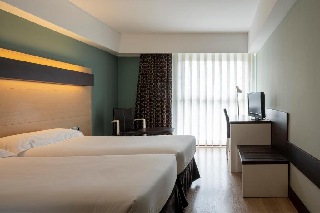 Un pat sau paturi într-o cameră la Hotel Ciudad de Logroño