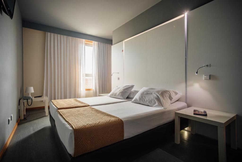 Cama ou camas em um quarto em Basic Braga by Axis