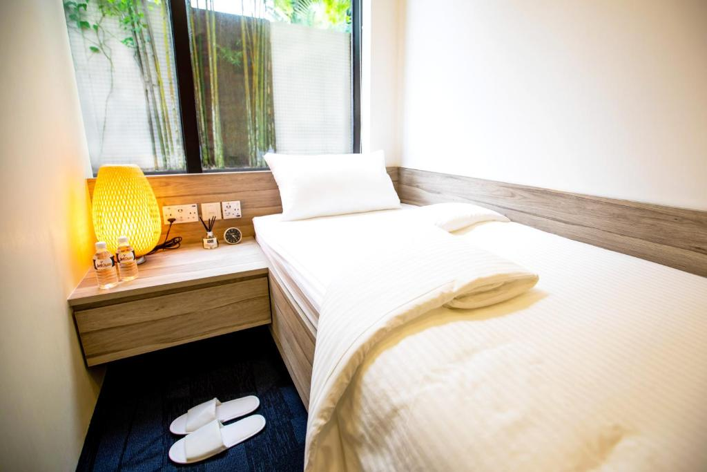 A bed or beds in a room at JetQuay Suites