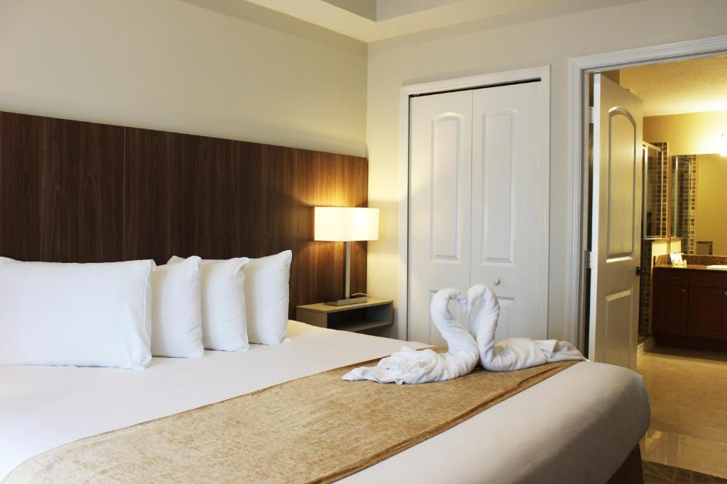 A bed or beds in a room at The Point Hotel & Suites Universal