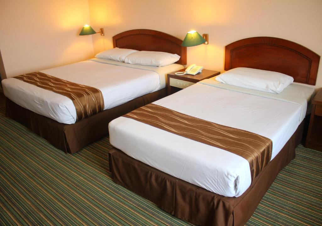 A bed or beds in a room at Hotel Seri Malaysia Port Dickson