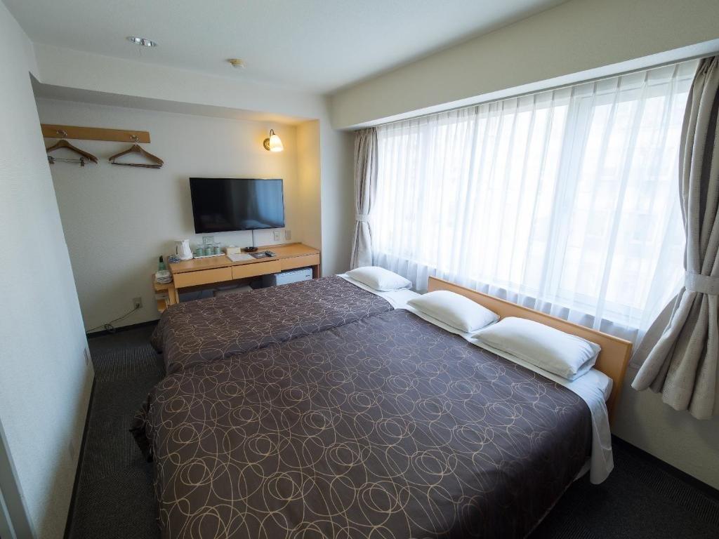 A bed or beds in a room at Hotel Shin Osaka