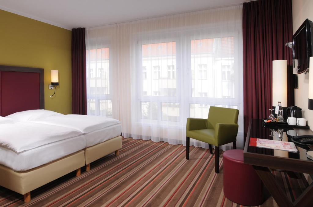 A bed or beds in a room at Leonardo Hotel Berlin