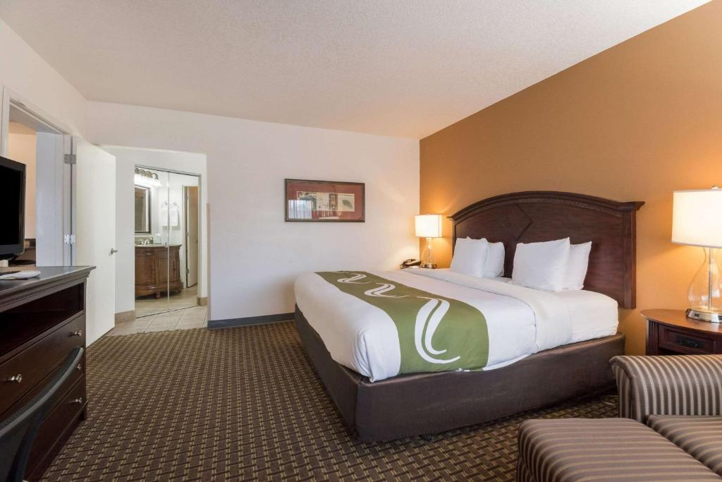 A bed or beds in a room at Quality Inn & Suites Airport