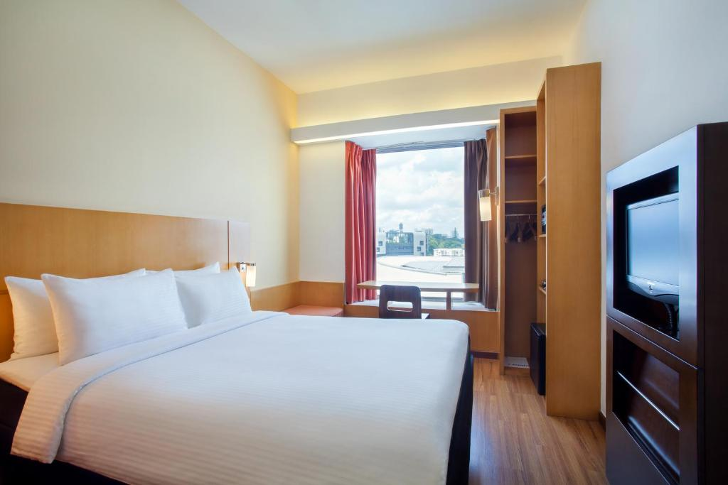 A bed or beds in a room at Ibis Singapore on Bencoolen