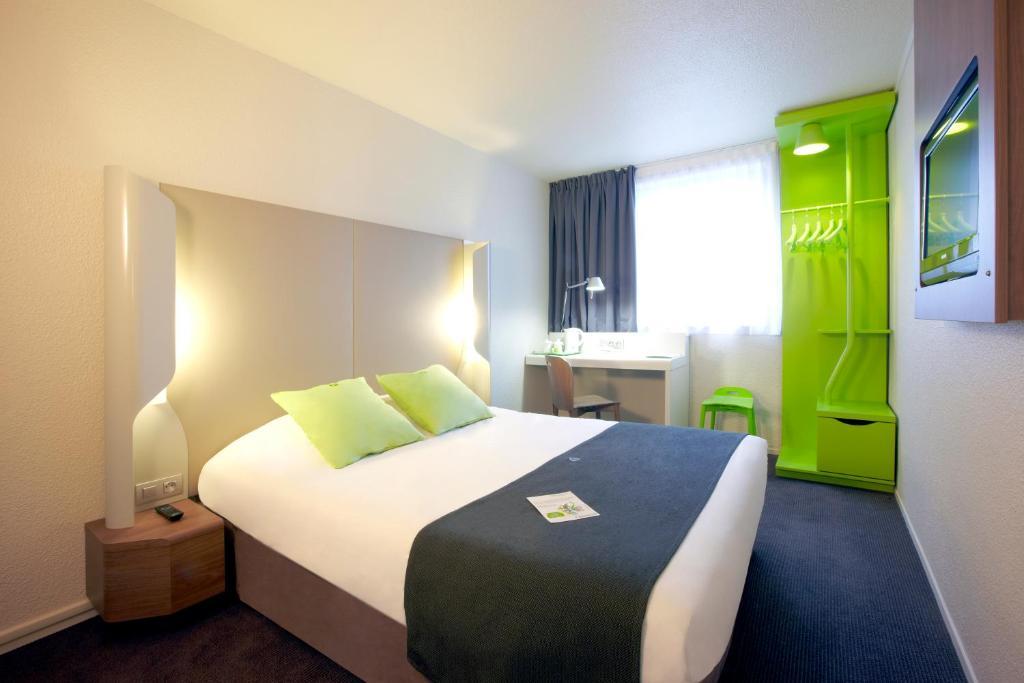 A bed or beds in a room at Campanile Paris 19 - La Villette