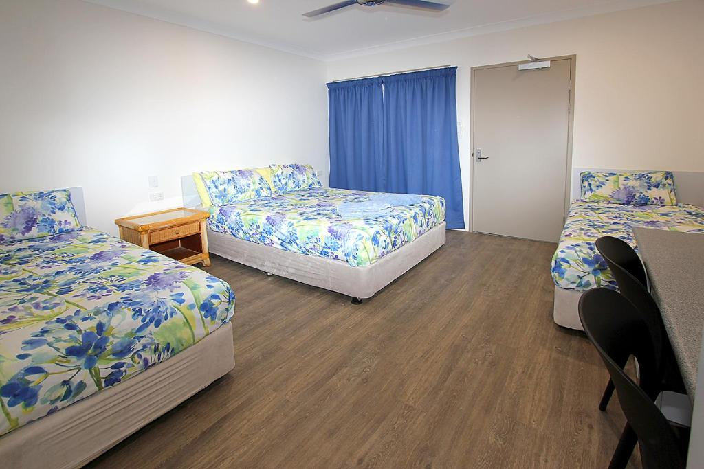 A bed or beds in a room at Reef Gardens Motel