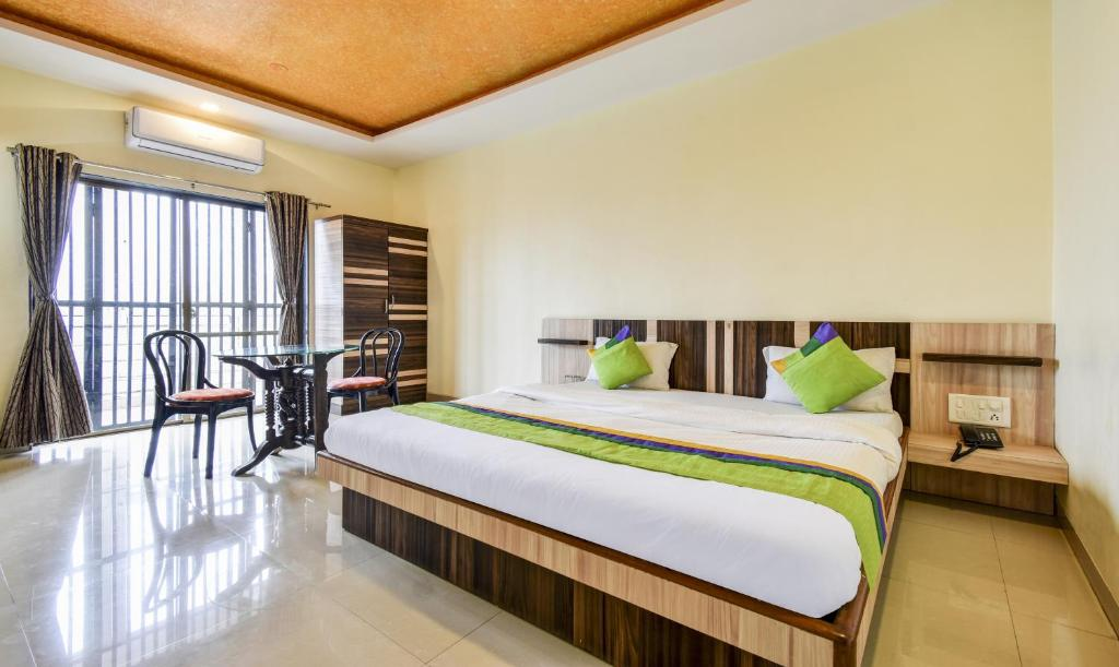 A bed or beds in a room at Treebo Trip Gugal Residency