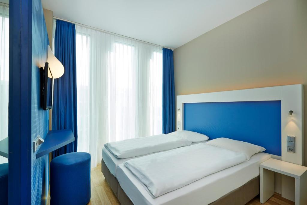 A bed or beds in a room at H2 Hotel München Messe