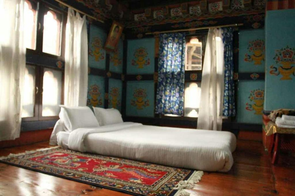 A bed or beds in a room at Chimi Lhakhang Village Homestay