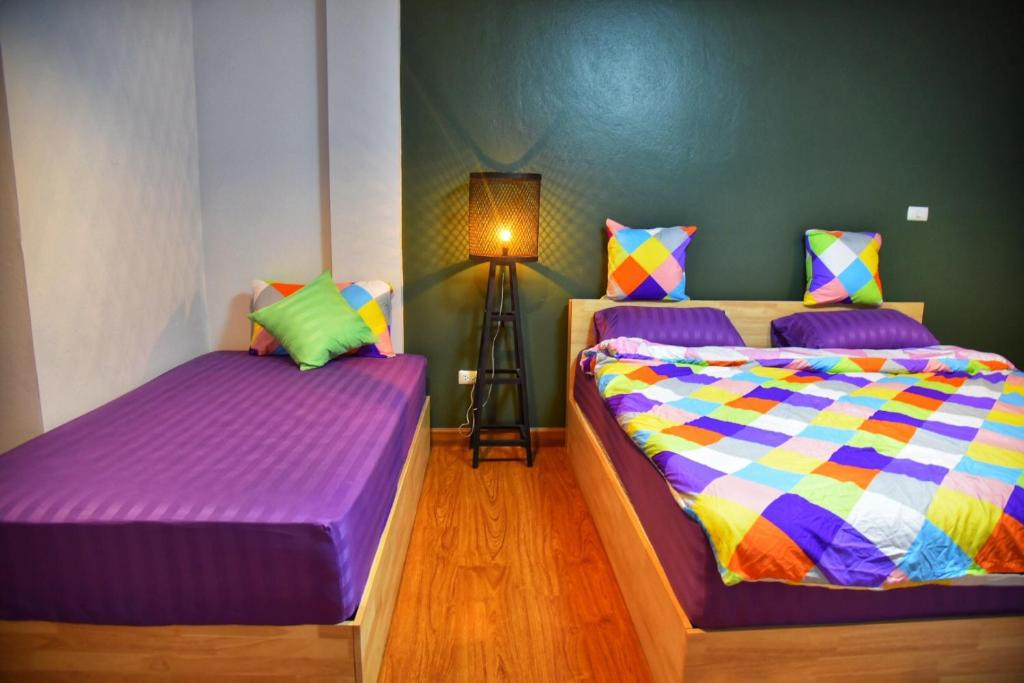 A bed or beds in a room at Manornpe มานอนเพ้ Hostel Chiang Mai