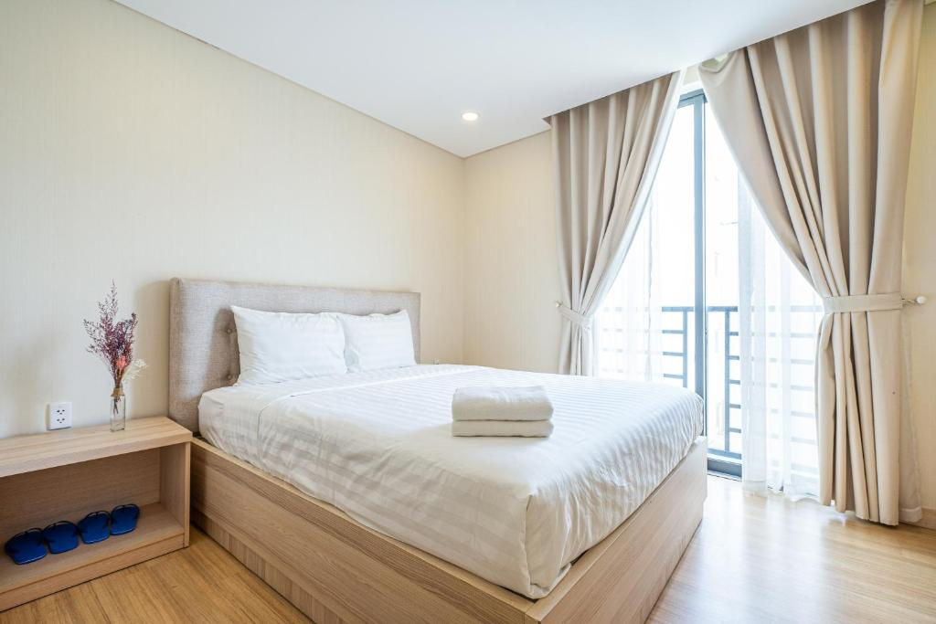 A bed or beds in a room at Luxy Park Hotel & Apartments - Notre Dame
