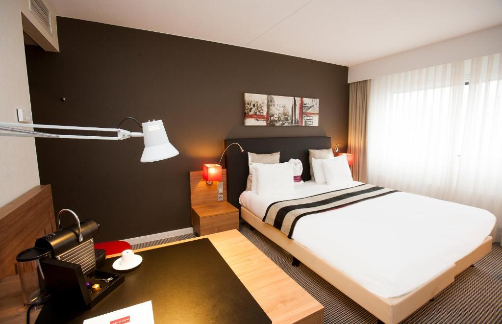 A bed or beds in a room at Mercure Hotel Den Haag Central
