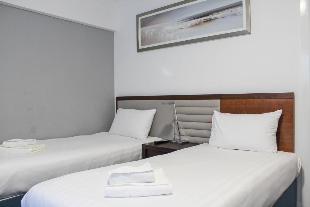 A bed or beds in a room at Heathrow Lodge