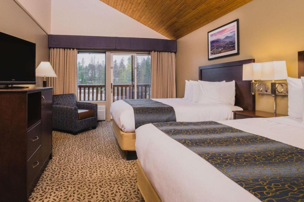 A bed or beds in a room at The Pine Lodge on Whitefish River, Ascend Hotel Collection