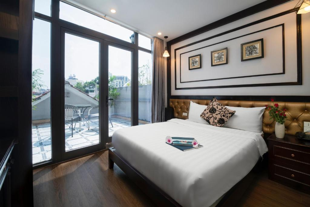 A bed or beds in a room at Le Beryl Hanoi Hotel