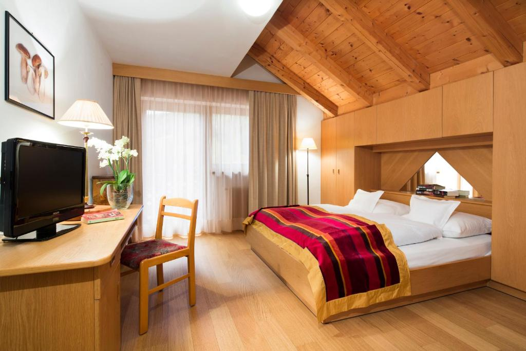 A bed or beds in a room at Ciasa Roby