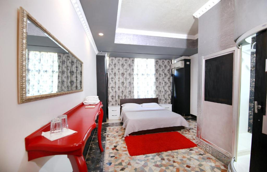 A bed or beds in a room at Hotel Eagle Tirana