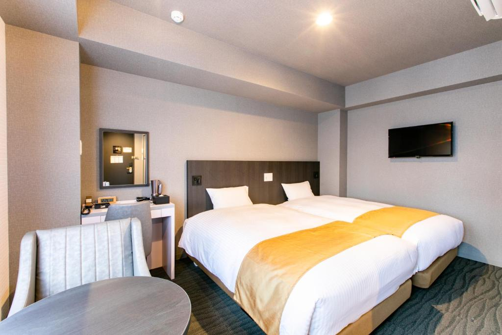 A bed or beds in a room at Hotel Wing International Shimbashi Onarimon