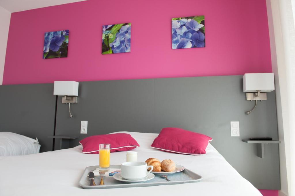 A bed or beds in a room at Logis L'Espadon