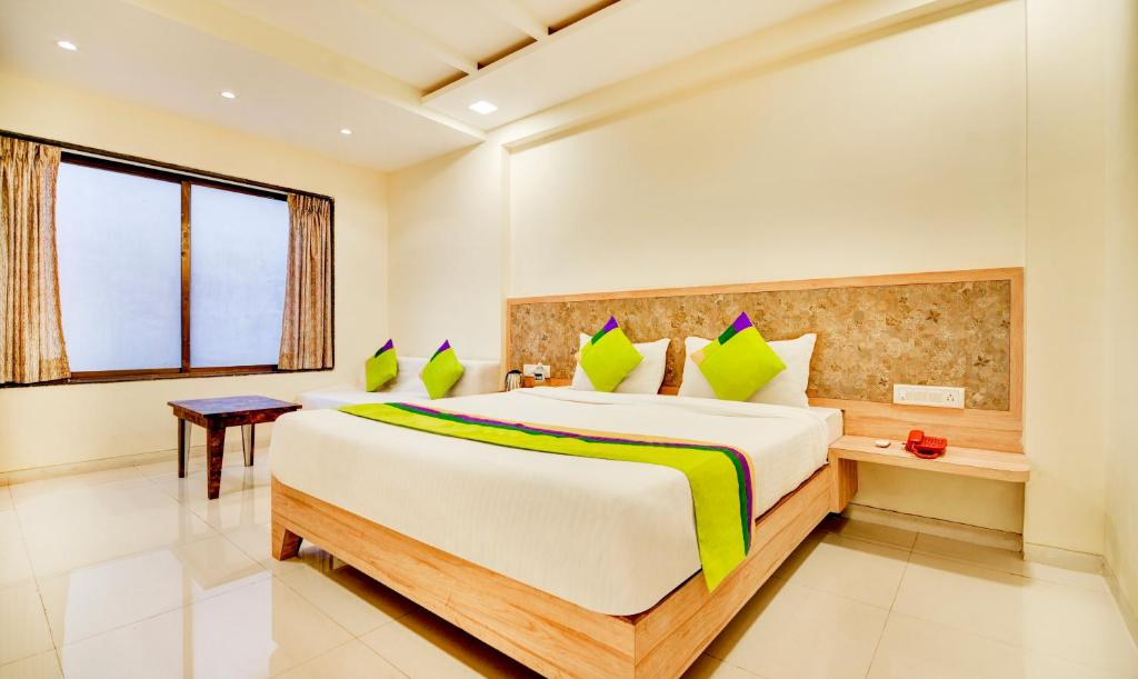 A bed or beds in a room at Treebo Trend Bright Plaza and Spa