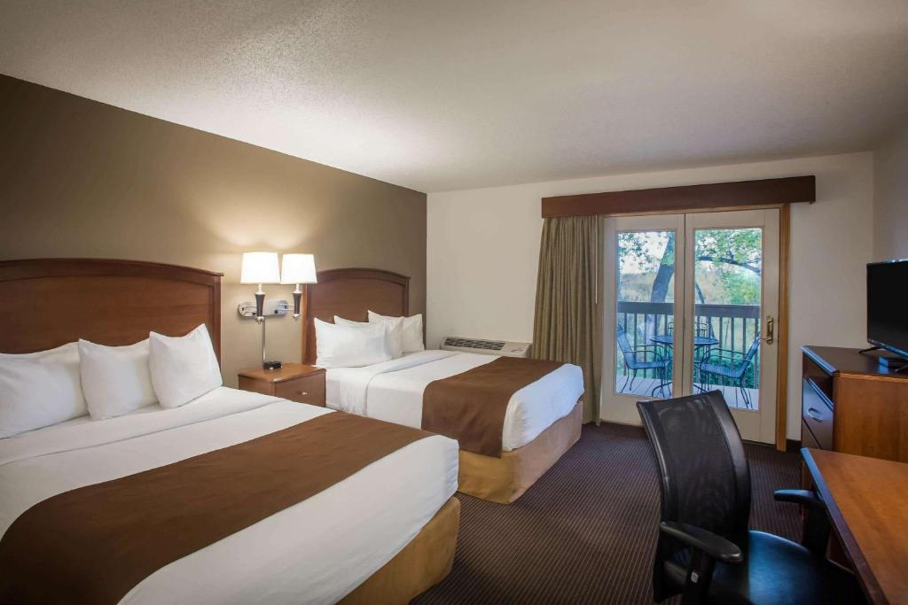 A bed or beds in a room at AmericInn by Wyndham Baudette