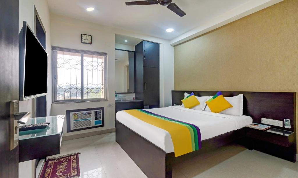 A bed or beds in a room at Treebo Trip Neeranand Plaza