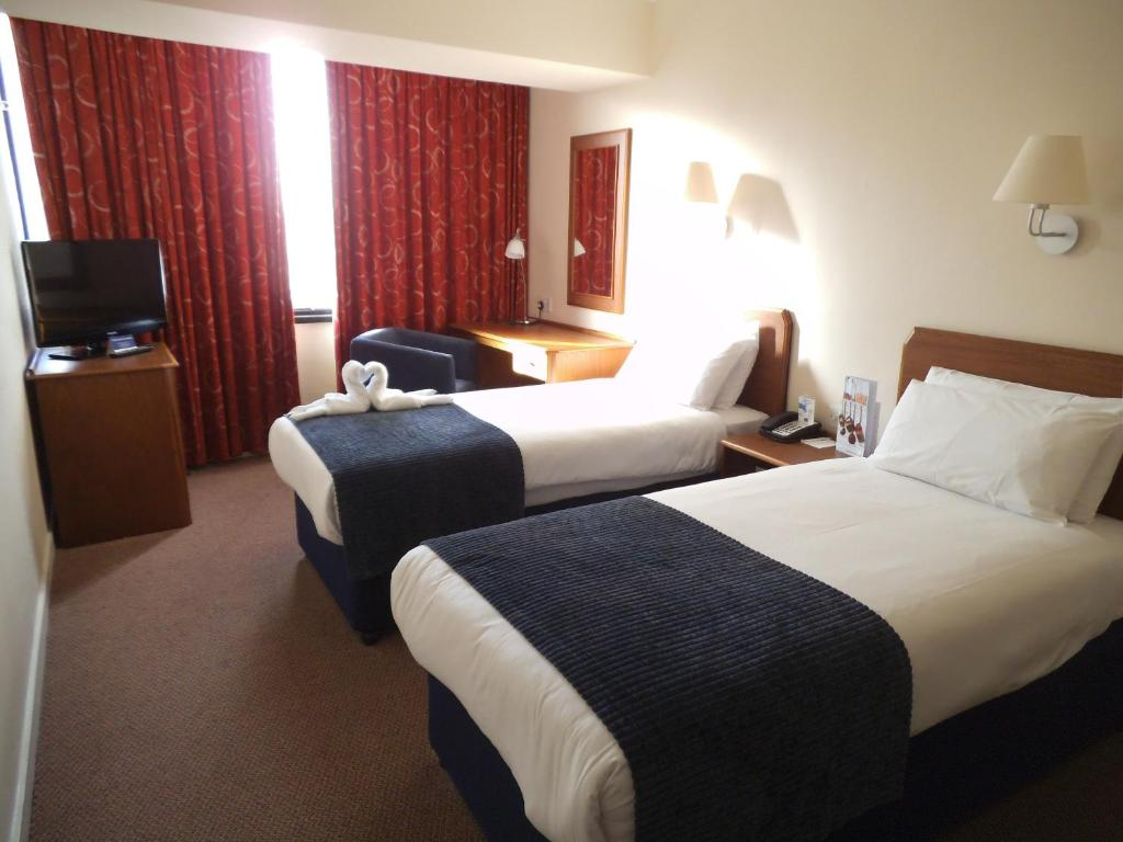 A bed or beds in a room at Airport Inn Gatwick