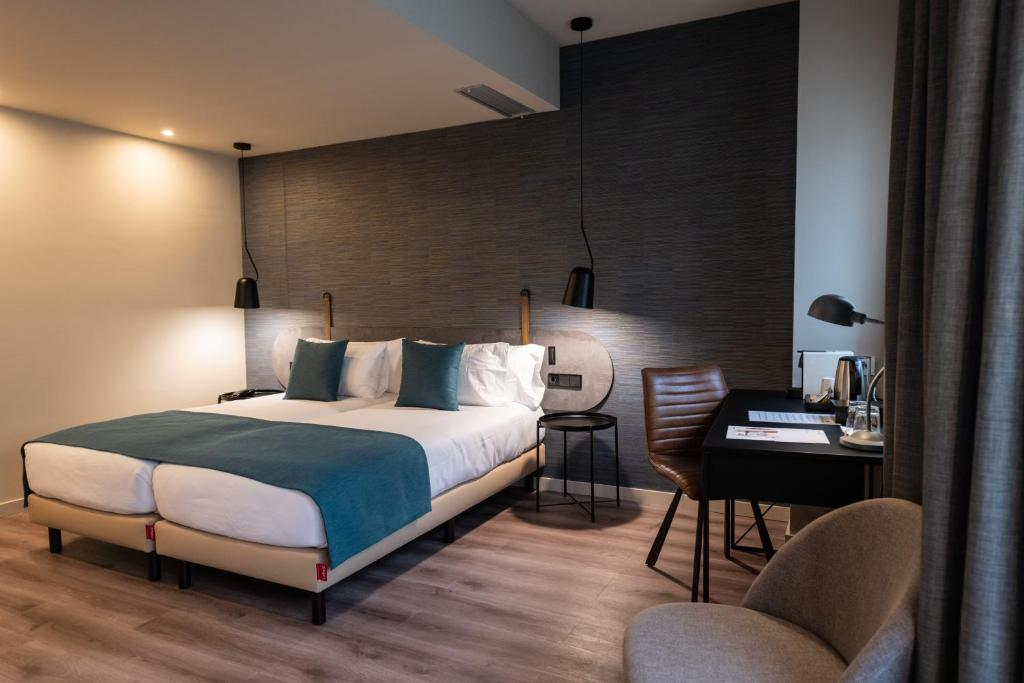 A bed or beds in a room at Atenea Rekord Suites