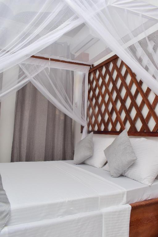 A bed or beds in a room at APCO Hotel Stone Town Zanzibar