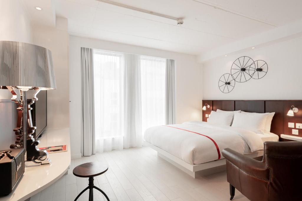 A bed or beds in a room at Ruby Lucy Hotel London