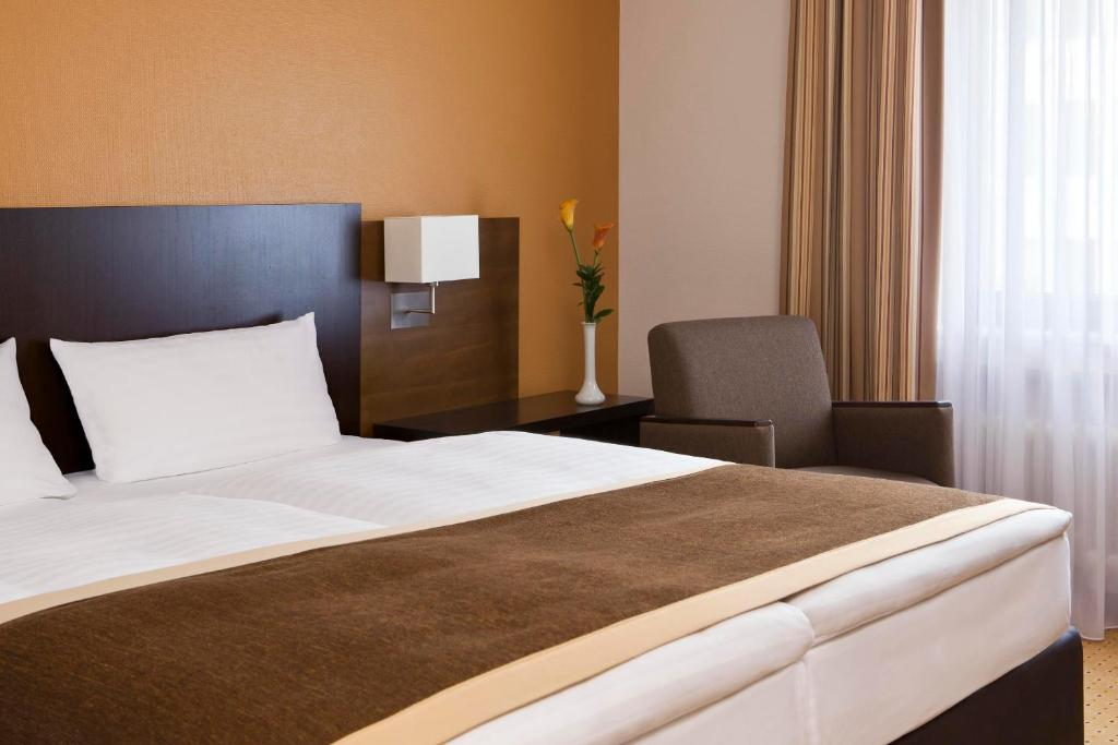 A bed or beds in a room at Trans World Hotel Donauwelle