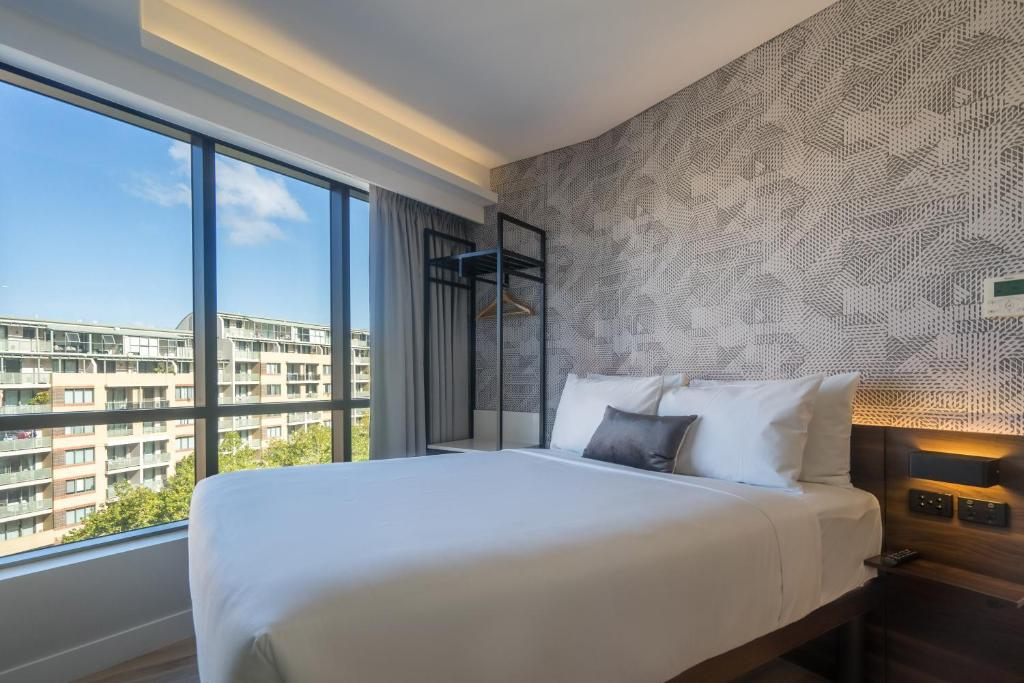 A bed or beds in a room at MetroResidences Darling Harbour