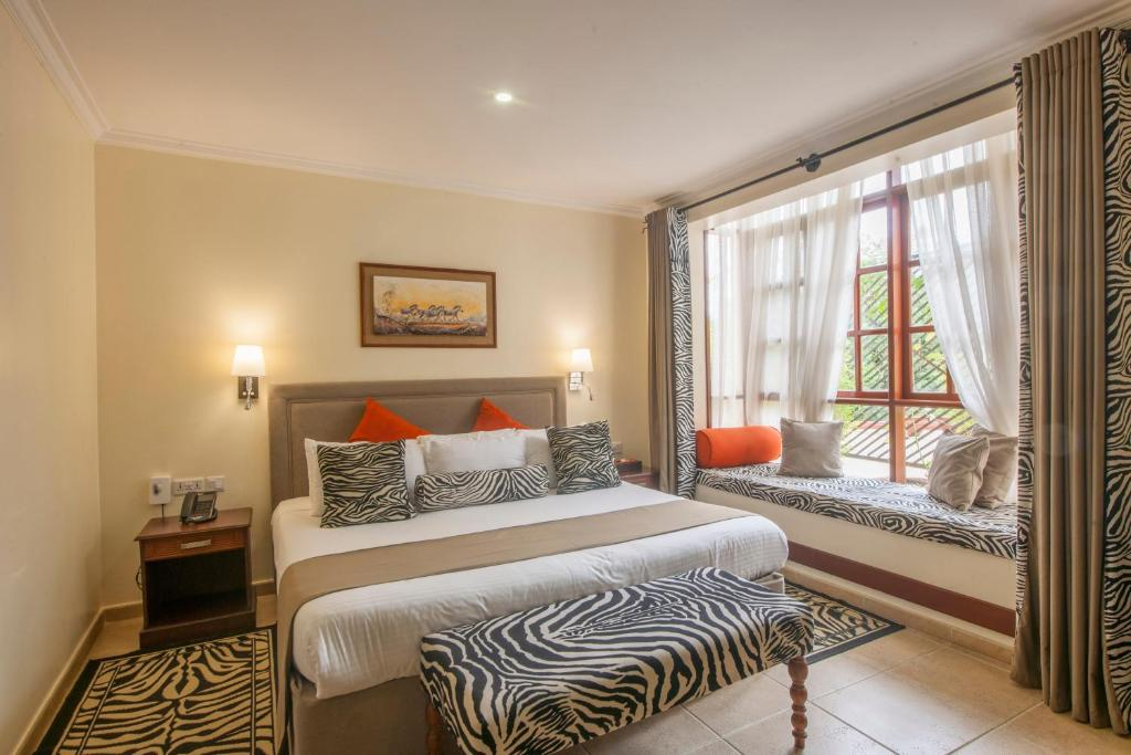A bed or beds in a room at African Tulip