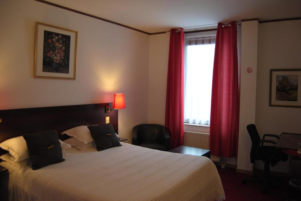 A bed or beds in a room at Hotel La Passerelle