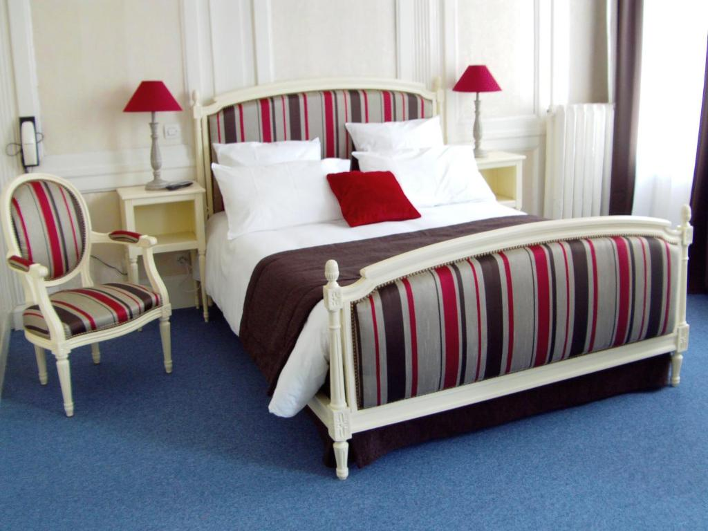 A bed or beds in a room at Le Grand Hotel