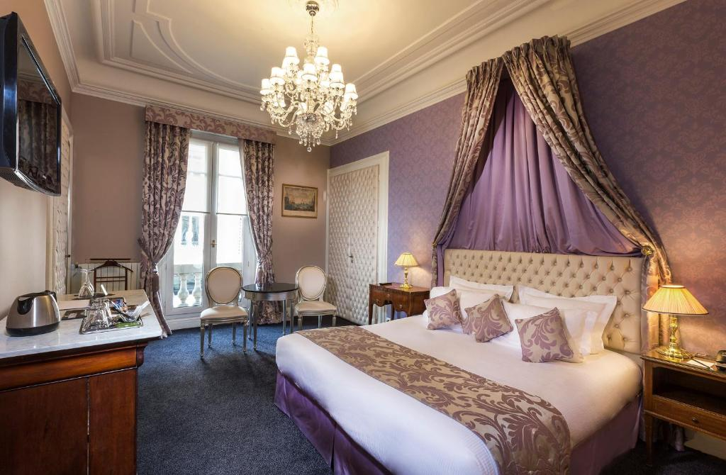 A bed or beds in a room at Hotel Claridge Paris