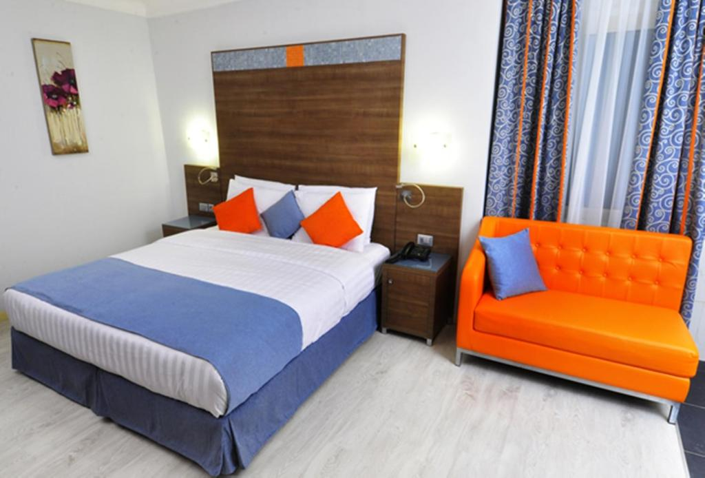 A bed or beds in a room at Bénin Royal Hôtel