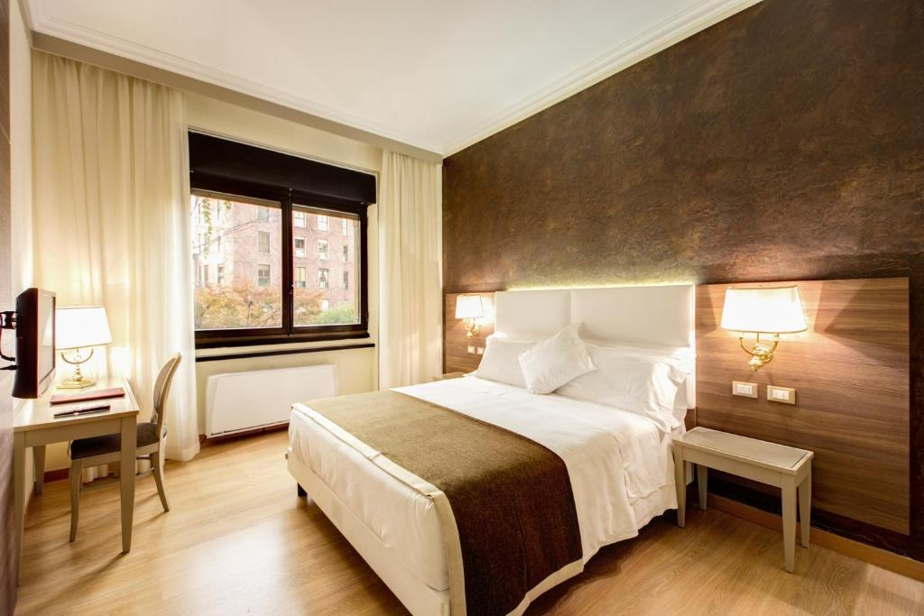 A bed or beds in a room at Hotel Romana Residence