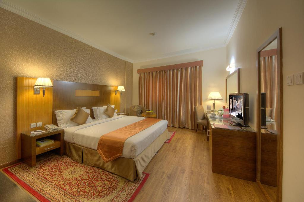 A bed or beds in a room at Fortune Pearl Hotel