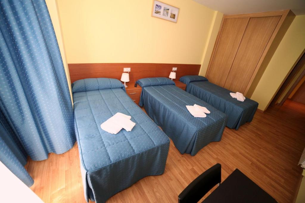 A bed or beds in a room at Pensión Palas