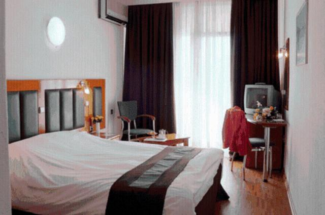 A bed or beds in a room at Elpida City Hotel