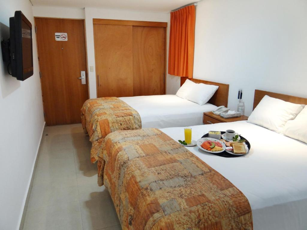 A bed or beds in a room at Hotel Suites Gaby