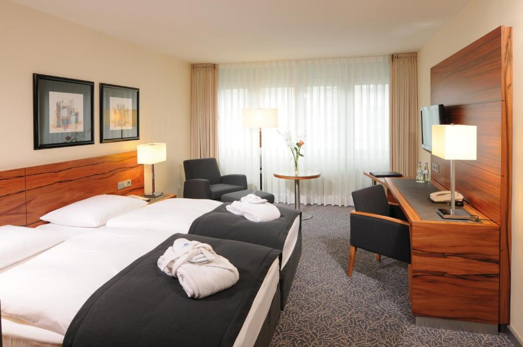 A bed or beds in a room at Maritim Hotel München