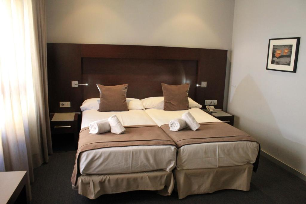 A bed or beds in a room at Hotel Madanis Liceo